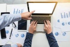 Un'immagine di due giovani uomini d'affari che lavorano con il computer portatile, compressa, smar immagine stock
