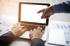 Un'immagine di due giovani uomini d'affari che lavorano con il computer portatile, la compressa e la f immagini stock