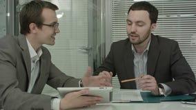Un'immagine di due giovani uomini d'affari facendo uso del touchpad a stock footage