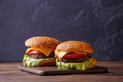 Un'immagine di due hamburger sulla tavola di legno Fotografia Stock