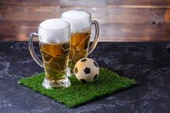 Un'immagine di due vetri di birra, pallone da calcio su erba verde Fotografia Stock Libera da Diritti