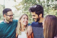 Un'immagine di quattro giovani amici sorridenti felici che camminano all'aperto Immagini Stock Libere da Diritti