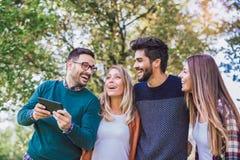 Un'immagine di quattro giovani amici sorridenti felici che camminano all'aperto Immagini Stock