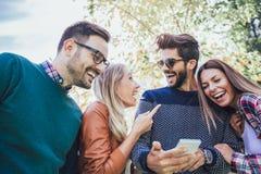 Un'immagine di quattro giovani amici sorridenti felici che camminano all'aperto Fotografia Stock Libera da Diritti