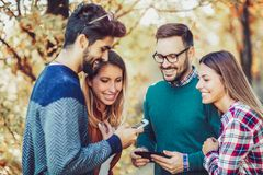 Un'immagine di quattro giovani amici sorridenti felici che camminano all'aperto nel parco Immagini Stock
