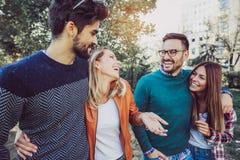 Un'immagine di quattro giovani amici sorridenti felici che camminano all'aperto nel parco Fotografia Stock