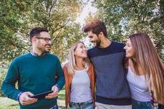 Un'immagine di quattro giovani amici sorridenti felici che camminano all'aperto nel parco Fotografie Stock Libere da Diritti
