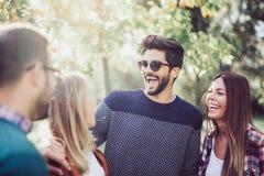 Un'immagine di quattro giovani amici sorridenti felici che camminano all'aperto nel parco del thhe Fotografia Stock