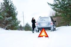 Un'immagine di una giovane donna che ha un problema con un'automobile su un wint Fotografie Stock Libere da Diritti