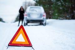 Un'immagine di una giovane donna che ha un problema con un'automobile su un wint Fotografie Stock