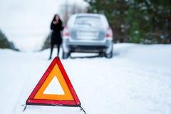 Un'immagine di una giovane donna che ha un problema con un'automobile su un wint Immagini Stock Libere da Diritti