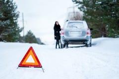 Un'immagine di una giovane donna che ha un problema con un'automobile su un wint Fotografia Stock Libera da Diritti