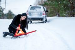 Un'immagine di una giovane donna che ha un problema con un'automobile su un wint Fotografia Stock