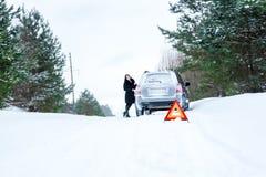 Un'immagine di una giovane donna che ha un problema con un'automobile su un wint Immagine Stock Libera da Diritti