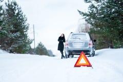 Un'immagine di una giovane donna che ha un problema con un'automobile su un wint Immagini Stock