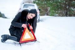 Un'immagine di una giovane donna che ha un problema con un'automobile su un wint Immagine Stock
