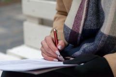 Un'immagine di una mano e di una penna che completare un formulario immagine stock libera da diritti