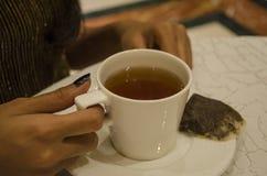 Un'immagine di una ragazza che tiene una tazza di tè Immagine Stock