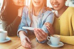 Un'immagine intersting delle ragazze di trhee in cui una di loro sta mostrando il suo test di gravidanza con il risultato positiv fotografia stock libera da diritti