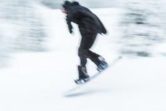 Un'immagine vaga molto veloce del bordo della neve di corsa con gli sci dell'uomo Immagine Stock