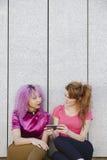 Un'immagine verticale della donna teenager due con i vestiti variopinti e l'operatore subacqueo Fotografie Stock