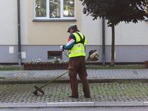 Un impiegato del servizio municipale della città rimuove il territorio Perfezionamento dell'area intorno alla casa Falciatura del immagini stock libere da diritti