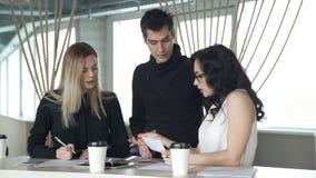 Un impiegato di concetto che si siede alla tavola, uomo di due femmine viene al posto di lavoro stock footage