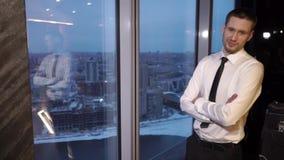 Un impiegato di concetto fa una pausa la finestra ed esamina la città archivi video