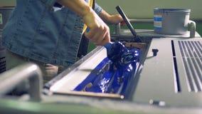 Un impiegato sta preparando la pittura blu in una stampatrice industriale video d archivio