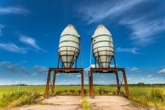Un'impressione artistica di due silos in un campo verde Fotografia Stock