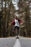 Un inconformista de risa joven en una camisa del casquillo y de tela escocesa está montando su longboard en una carretera naciona Imagen de archivo