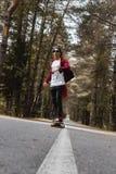 Un inconformista joven en una camisa del casquillo y de tela escocesa está montando su longboard en una carretera nacional en el  Fotos de archivo libres de regalías