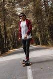 Un inconformista joven en una camisa del casquillo y de tela escocesa está montando su longboard en una carretera nacional en el  Imágenes de archivo libres de regalías
