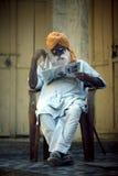 Un indiano dai capelli grigi, un uomo anziano che si siede in una sedia e che legge un giornale Fotografia Stock