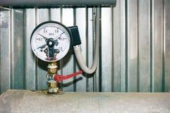 Un indicateur de pression avec des contacts électriques et un fil relié installé sur la canalisation photos libres de droits