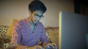 Un indio hermoso Guy Who Works Behind un ordenador portátil que se sienta en casa en un sofá almacen de video