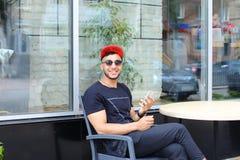 Un individuo árabe hermoso joven utiliza el teléfono, sienta la charla, sonríe Imagen de archivo