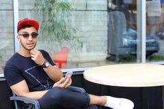 Un individuo árabe hermoso joven utiliza el teléfono, sienta la charla, sonríe Foto de archivo libre de regalías