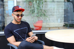 Un individuo árabe hermoso joven utiliza el teléfono, sienta la charla y se sienta Fotografía de archivo
