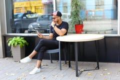 Un individuo árabe lindo joven utiliza el teléfono, sienta la charla, sonrisas y Imagen de archivo