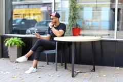 Un individuo árabe lindo joven utiliza el teléfono, sienta la charla, sonrisas y Fotos de archivo