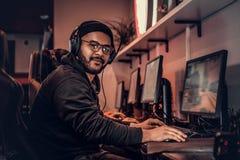 Un individuo afroamericano joven, gozando pasando tiempo con sus amigos, jugando en un videojuego multijugador en una PC en a fotografía de archivo libre de regalías