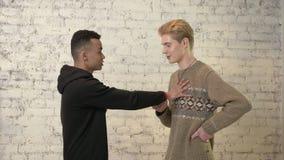 Un individuo americano joven con el pelo rubio intenta besar a su amigo africano, pero él está contra él LGBT, homosexualidad, ga metrajes