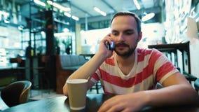 Un individuo barbudo joven que habla en el teléfono que se sienta en un café de la ciudad metrajes