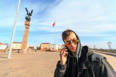 Un individuo blanco joven hermoso en gafas de sol está hablando en un móvil Imagen de archivo libre de regalías