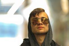 Un individuo blanco joven hermoso en gafas de sol y en la capilla Imagen de archivo libre de regalías