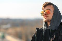 Un individuo blanco joven hermoso en gafas de sol y en la capilla Fotos de archivo libres de regalías