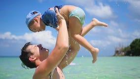 Un individuo con los juegos del niño que se divierten en el mar almacen de video