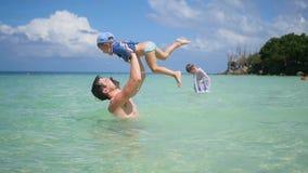 Un individuo con los juegos del niño que se divierten en el mar El bucear metrajes