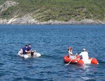 Un individuo con una muchacha en un rowing inflable rojo del barco en el mar Los medios del rescate del equipo de una travesía na foto de archivo libre de regalías
